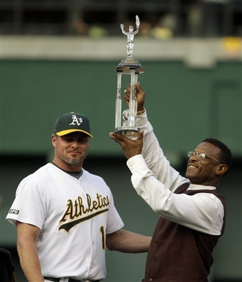 Rickey holding a trophy presented by Jason Giambi